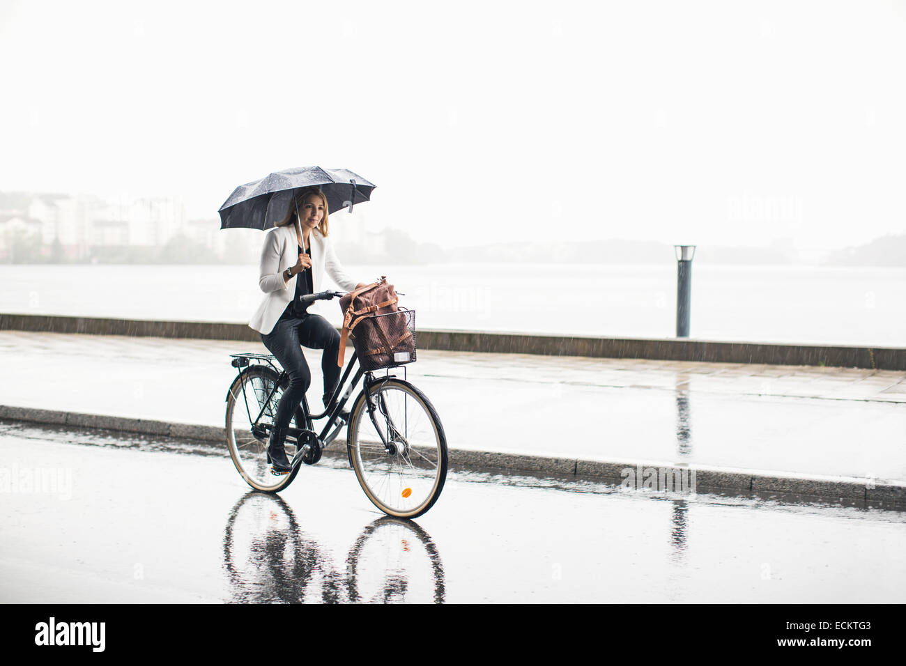 Full length of businesswoman riding bicycle on wet city street during rainy season - Stock Image