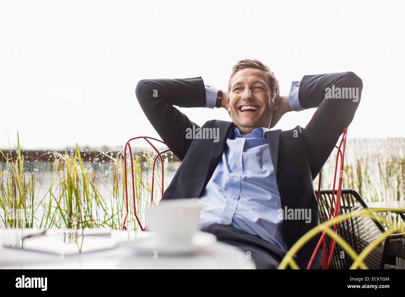 Happy businessman relaxing at outdoor cafe against clear sky - Stock Image