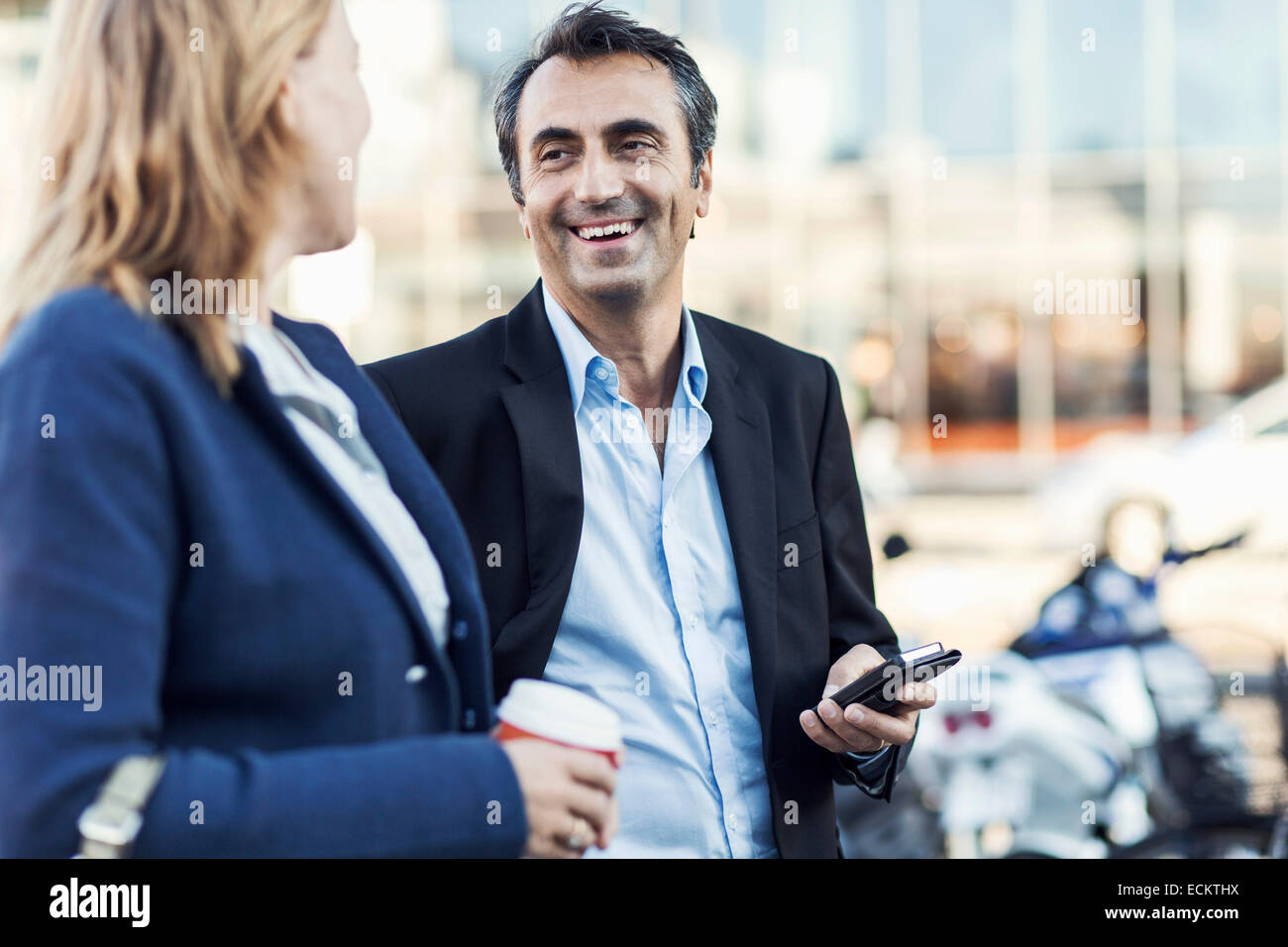 Happy businessman talking to female colleague outdoors Stock Photo