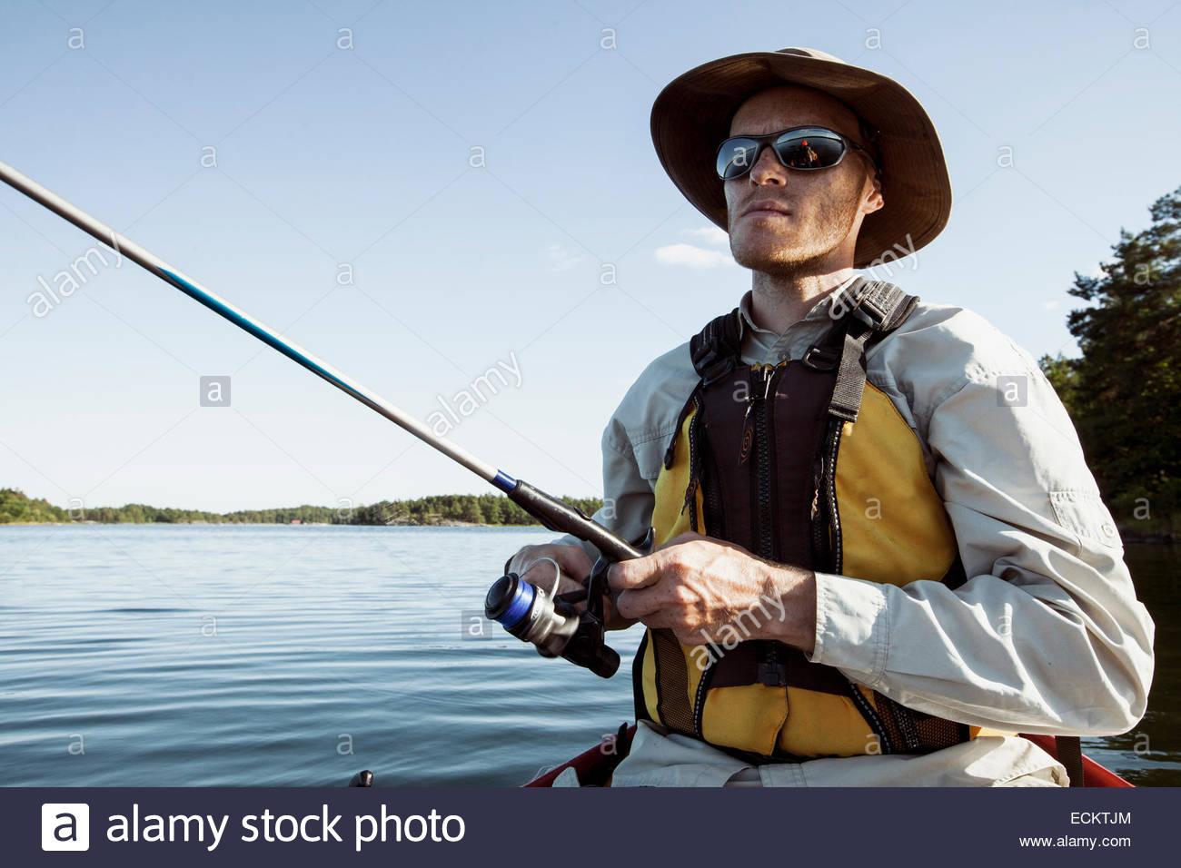 Man holding fishing rod in lake - Stock Image