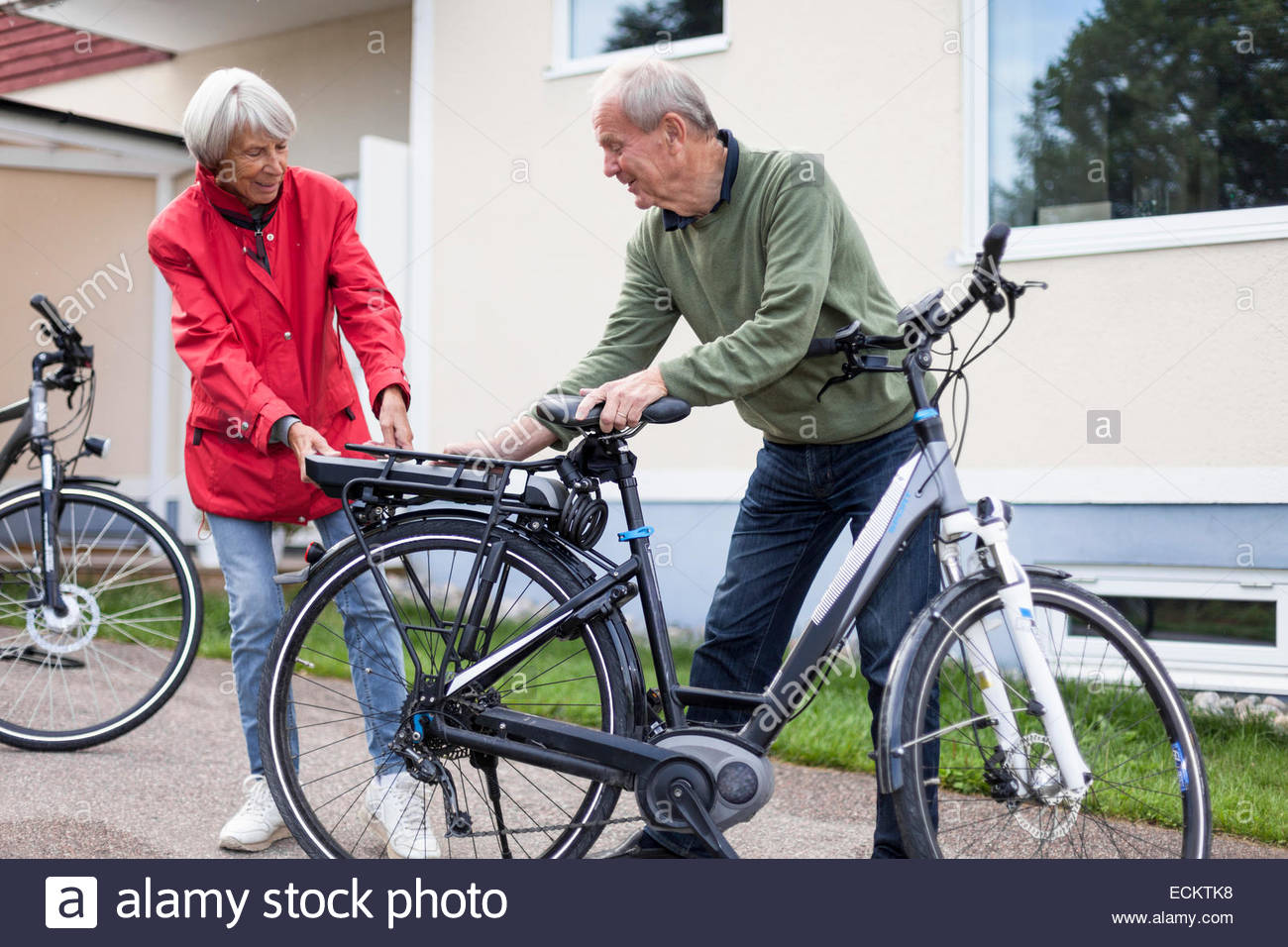 Senior couple inserting battery in backseat of electric bicycle outside house - Stock Image