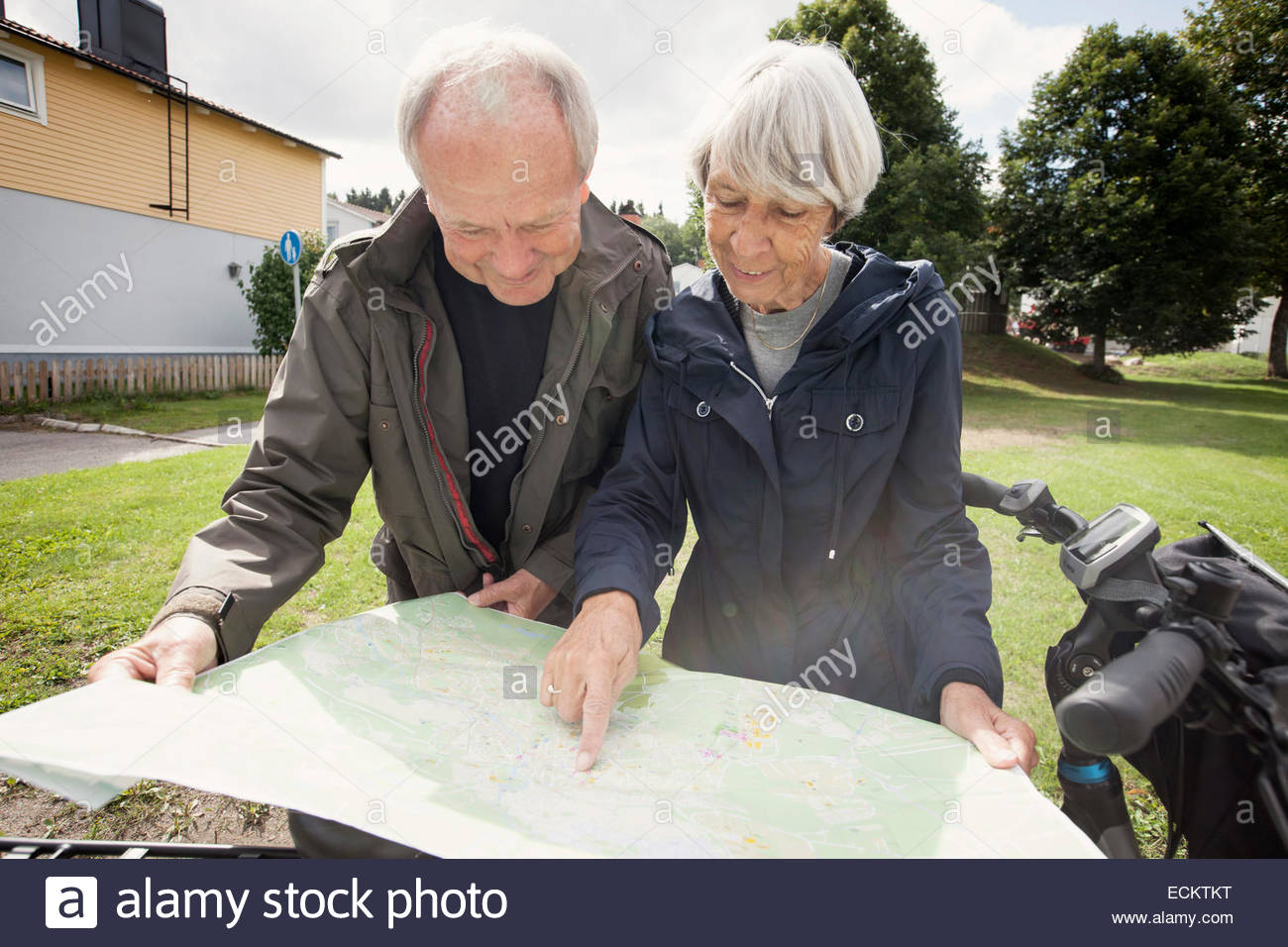 Senior couple reading map by bicycle at yard - Stock Image