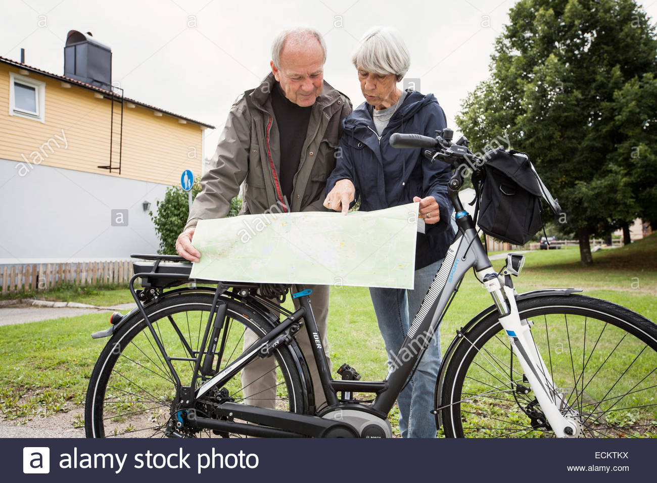 Senior couple searching places on map by bicycle at yard - Stock Image