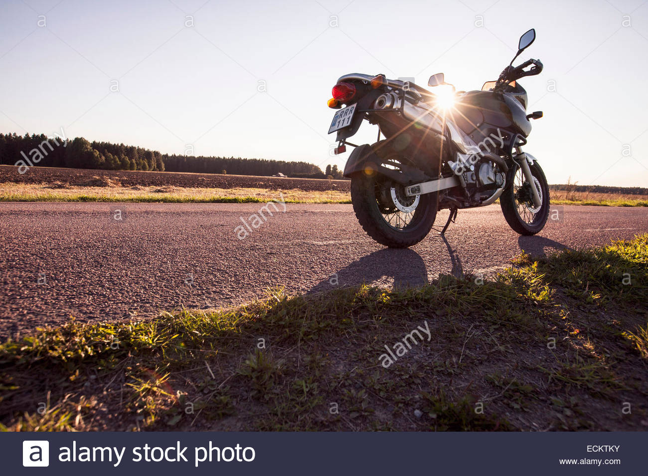 Motorcycle parked on country road - Stock Image