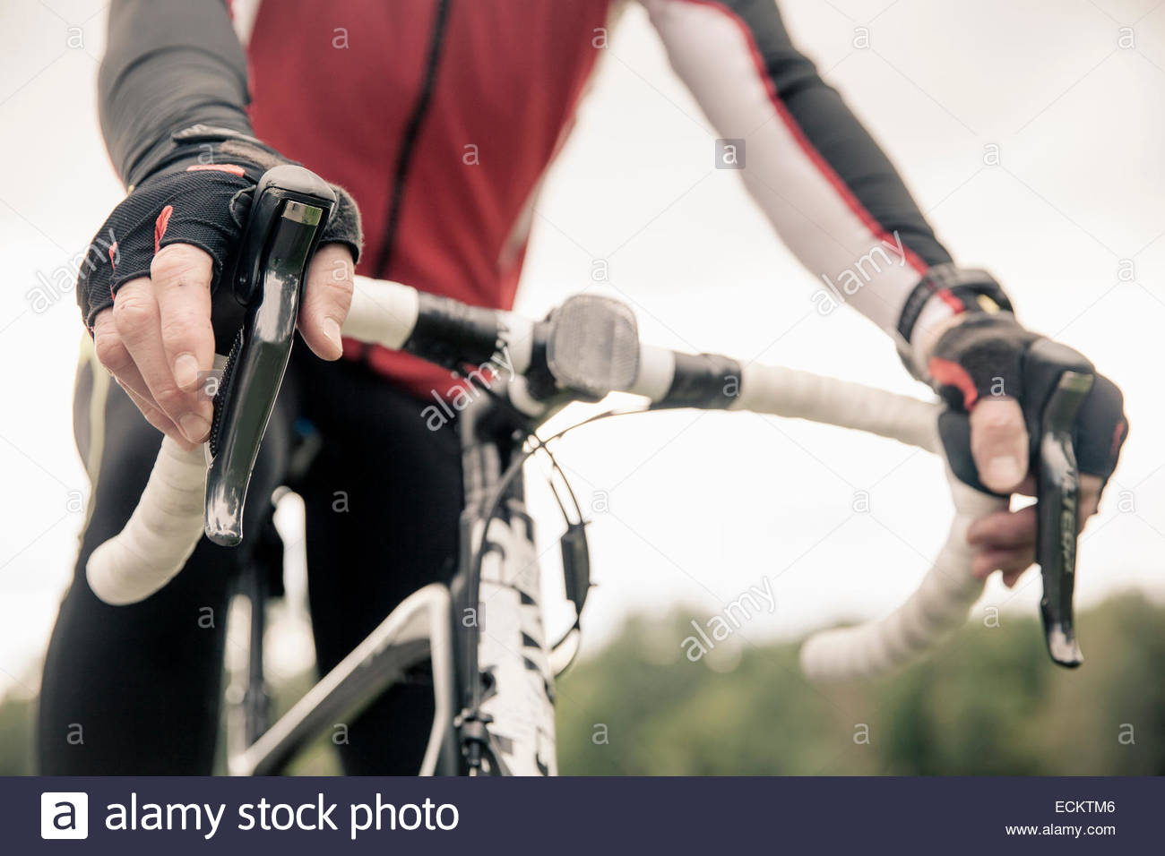 Midsection of cyclist sitting on mountain bike against clear sky - Stock Image