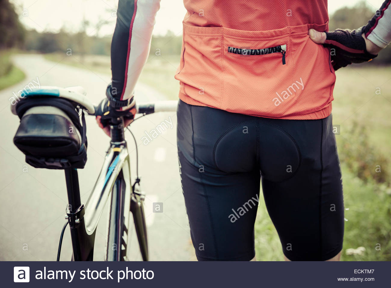 Rear view midsection of cyclist standing by bicycle on country road - Stock Image