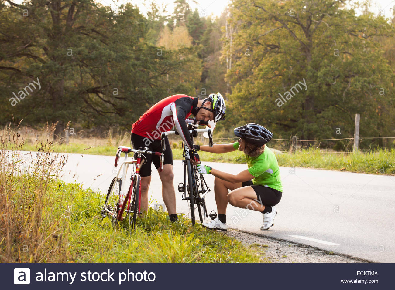 Cycling couple repairing mountain bike on country road - Stock Image
