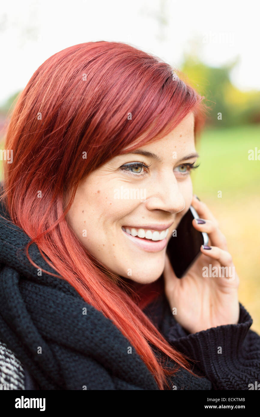 Happy mid adult woman talking on smart phone in park - Stock Image