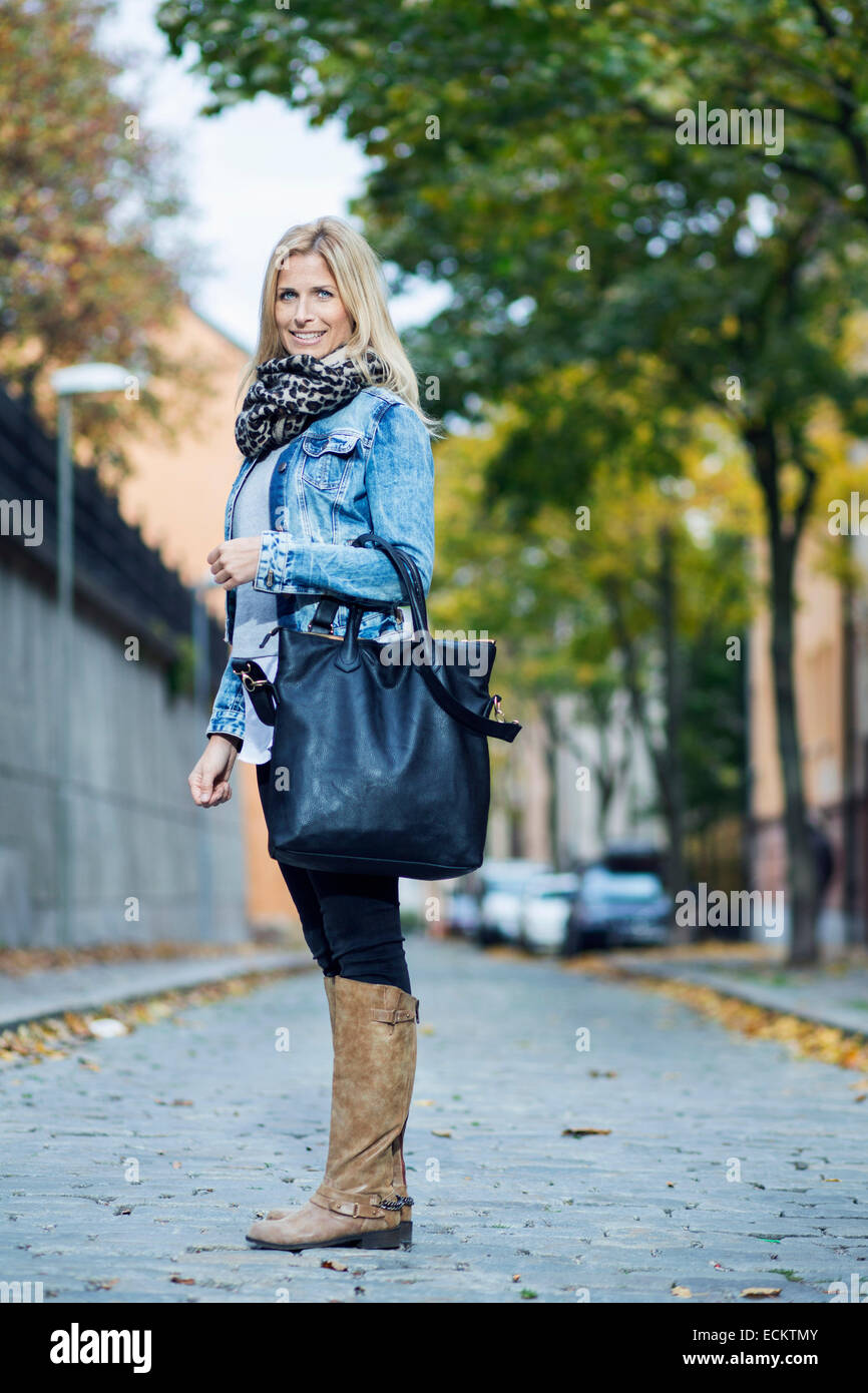 Full length portrait of mid adult woman standing on street - Stock Image