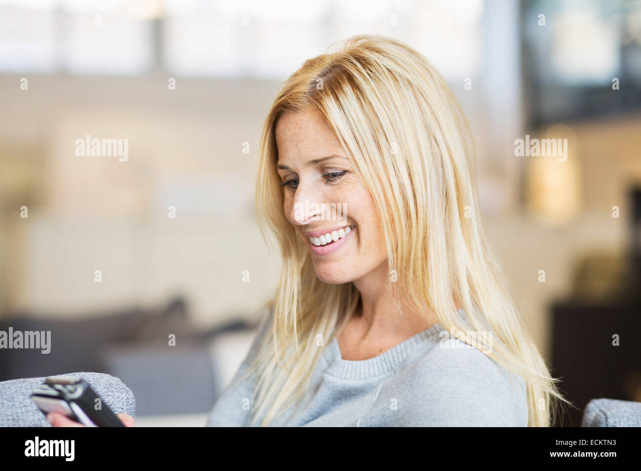 Happy mid adult woman using smart phone at home - Stock Image