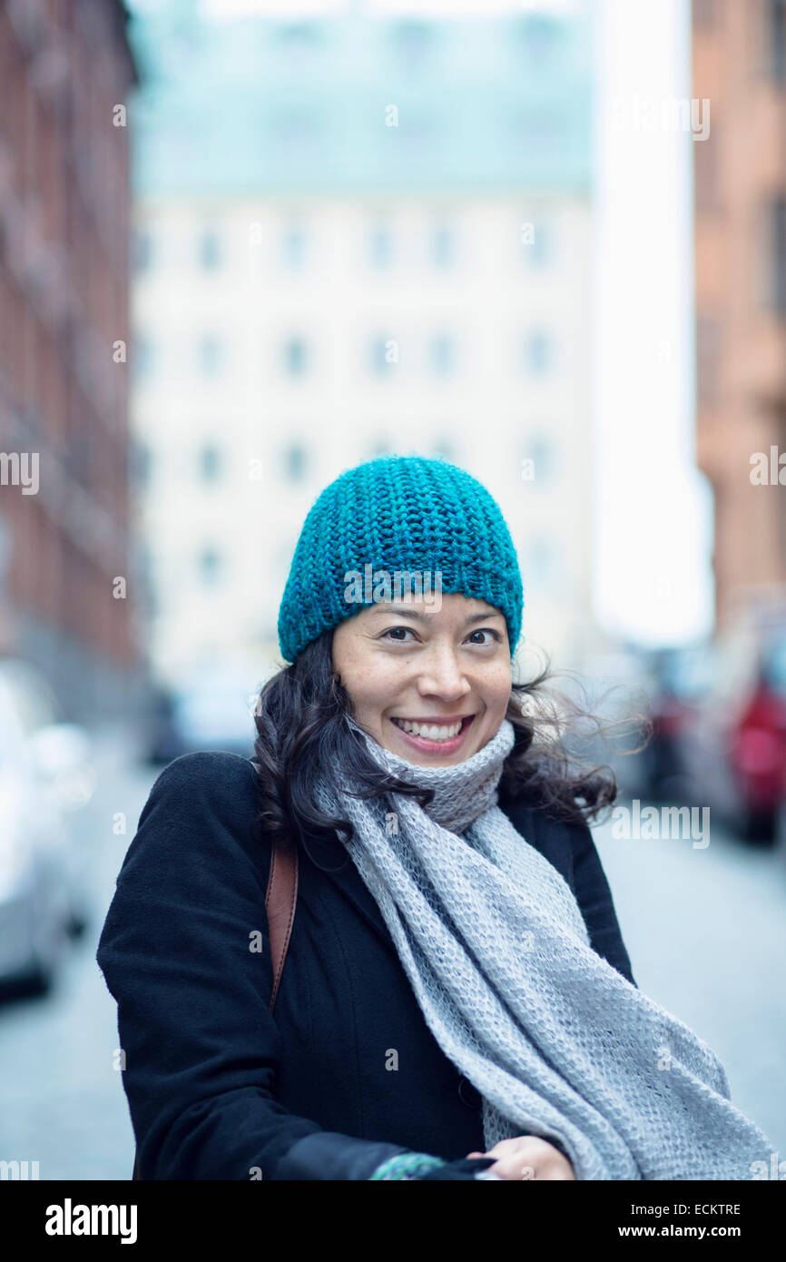 Portrait of happy woman in city street - Stock Image