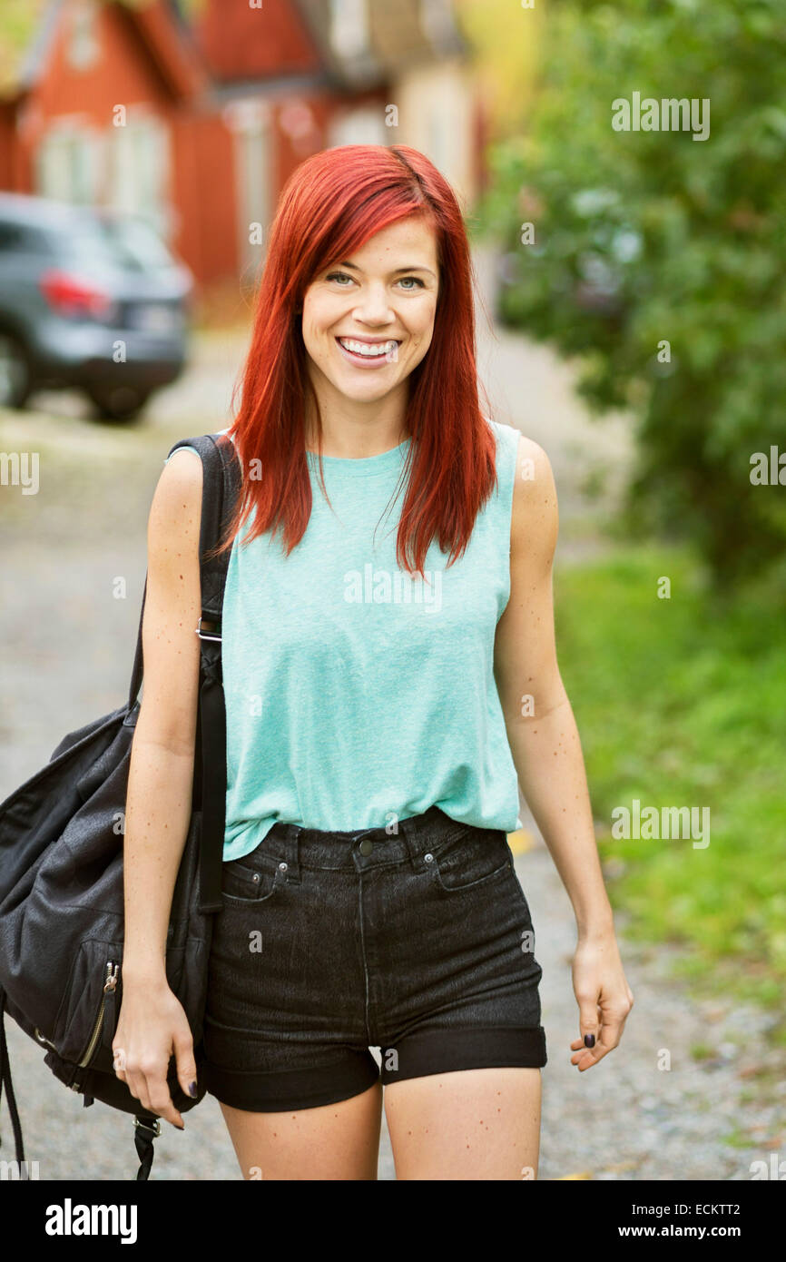 Portrait of happy mid adult woman walking on street - Stock Image
