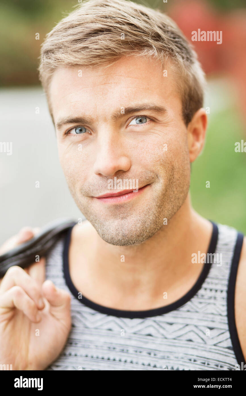 Portrait of smiling young man outdoors - Stock Image