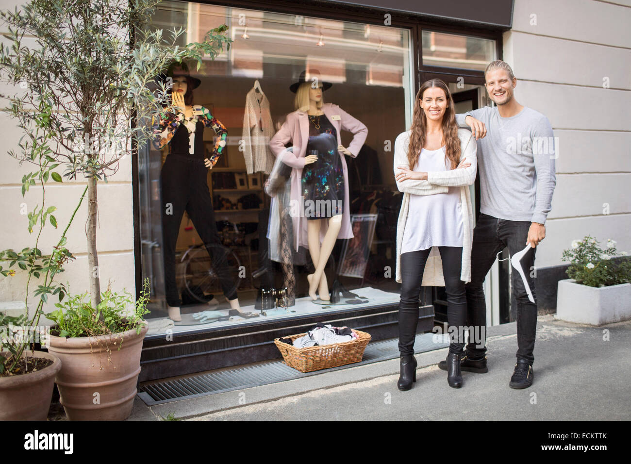 Portrait of smiling owner with female worker standing in front of clothing store - Stock Image
