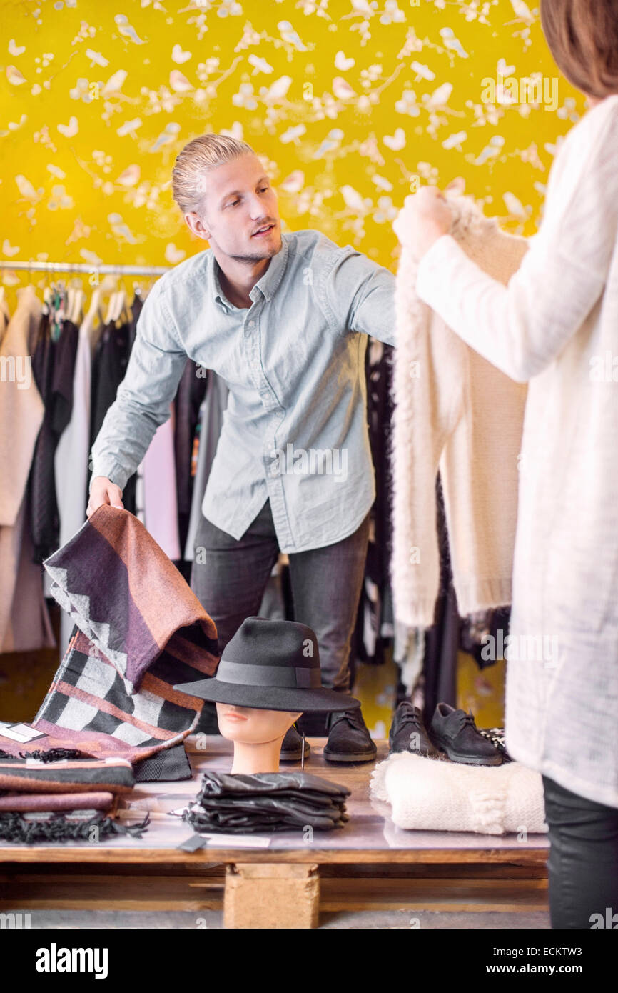 Male owner helping female customer in boutique Stock Photo