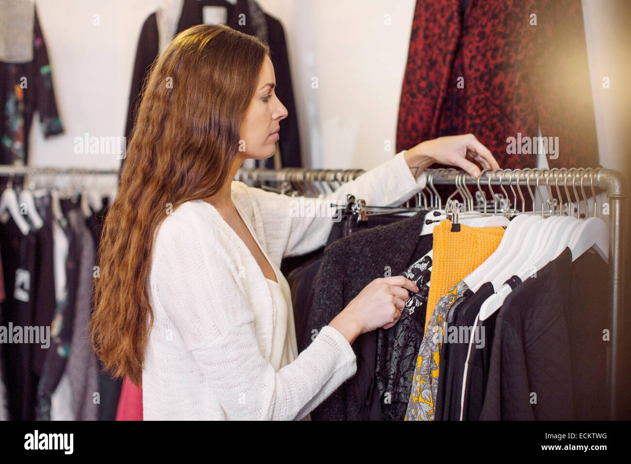 Female sales person arranging cloths in clothing store - Stock Image