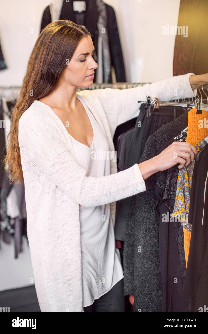 Female sales person arranging cloths in boutique Stock Photo