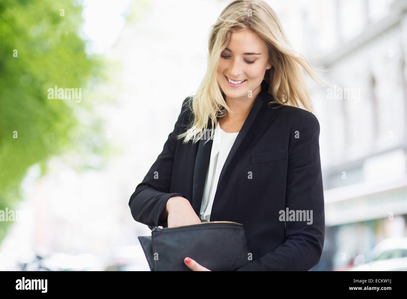 Smiling young woman searching something in her clutch bag outdoors - Stock Image