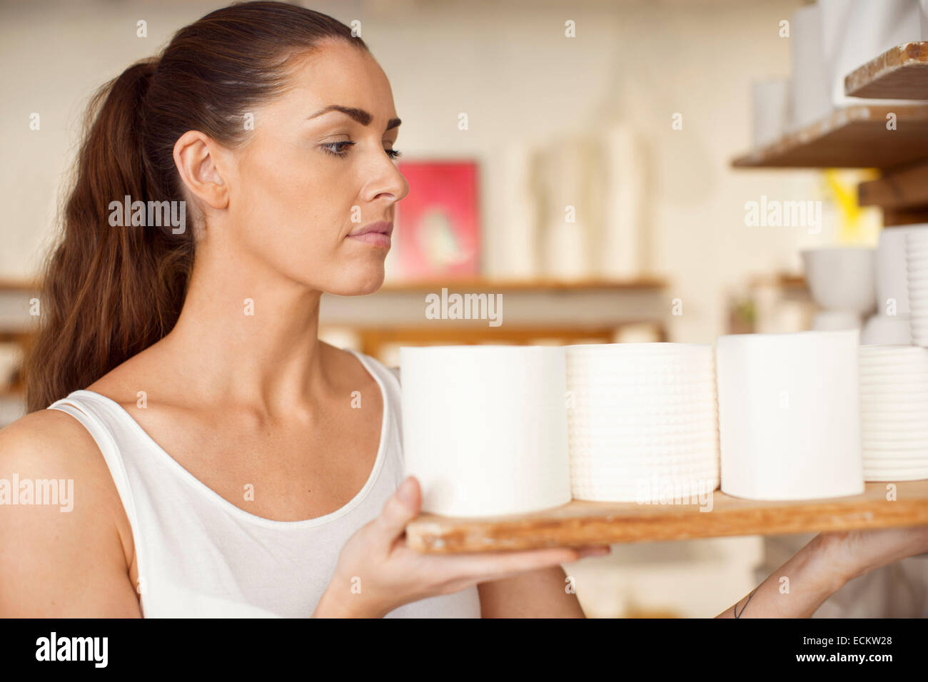 Female worker arranging craft products in crockery workshop - Stock Image