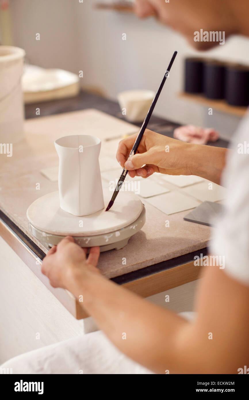 Young male worker painting pottery in crockery workshop - Stock Image