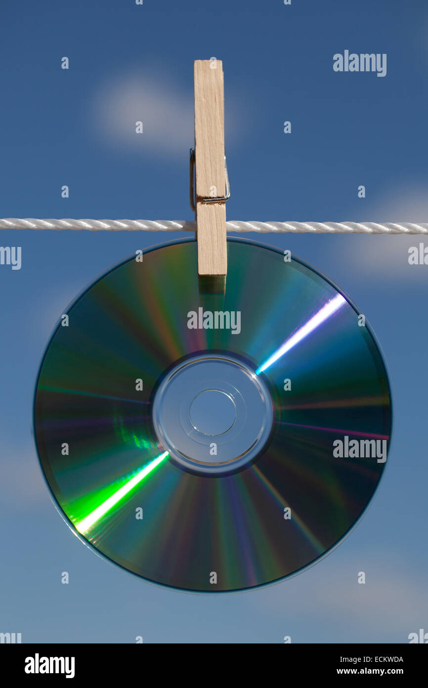 A CDs on a clothesline attached with clothespin. - Stock Image