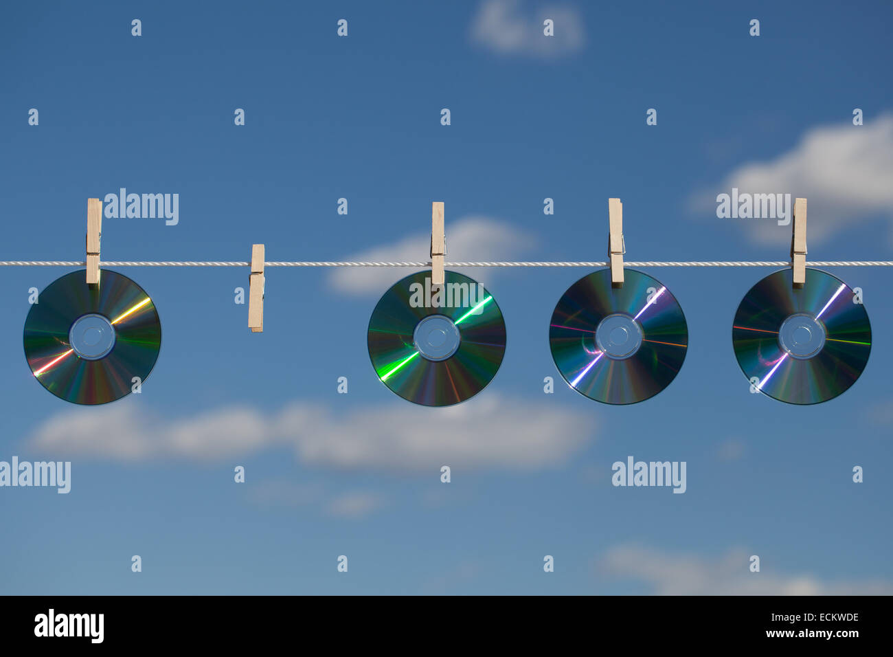 A missing CD in the row on a clothesline, attached with clothespins. - Stock Image