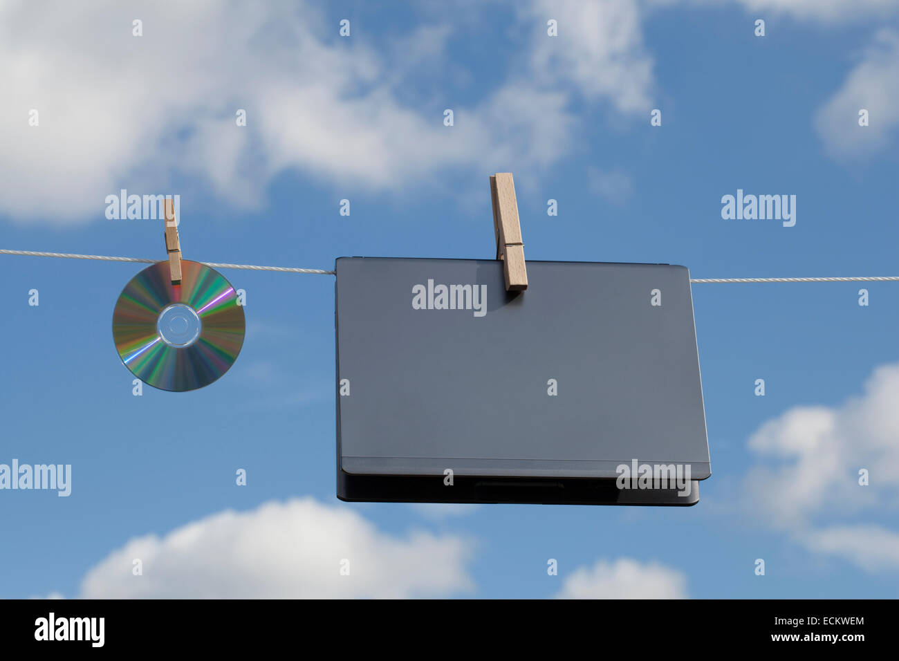 Laptop and a CD hanged on a clothesline. - Stock Image