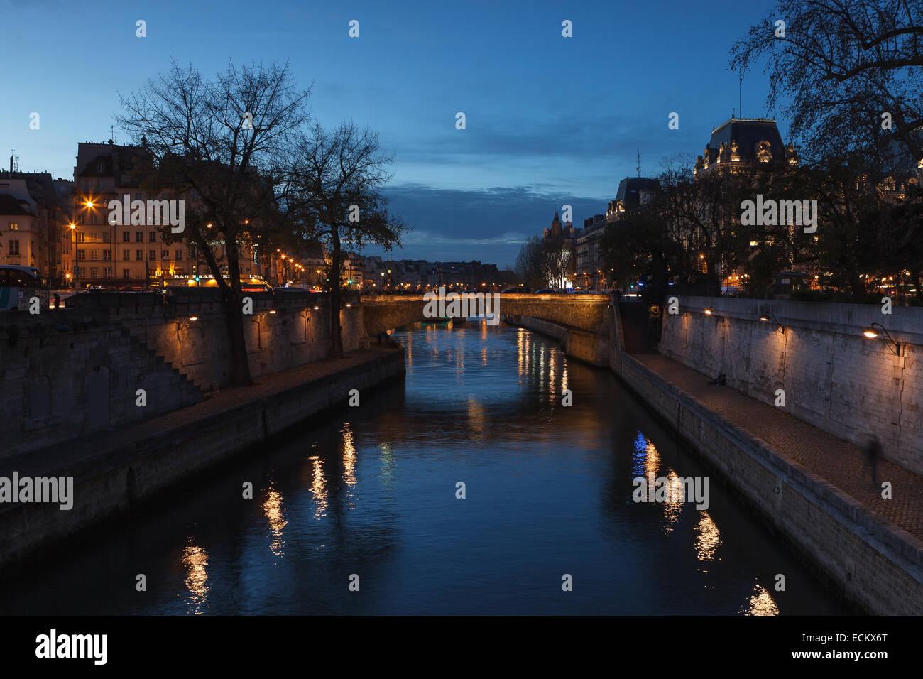 View of Paris and the Seine River at dusk from 'Pont au Double', near Notre Dame Cathedral. Paris, Ile de - Stock Image