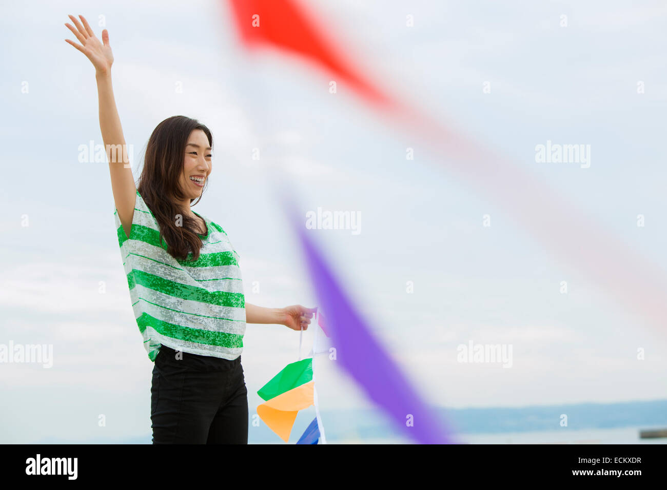 A woman on a beach in Kobe holding paper flags. - Stock Image