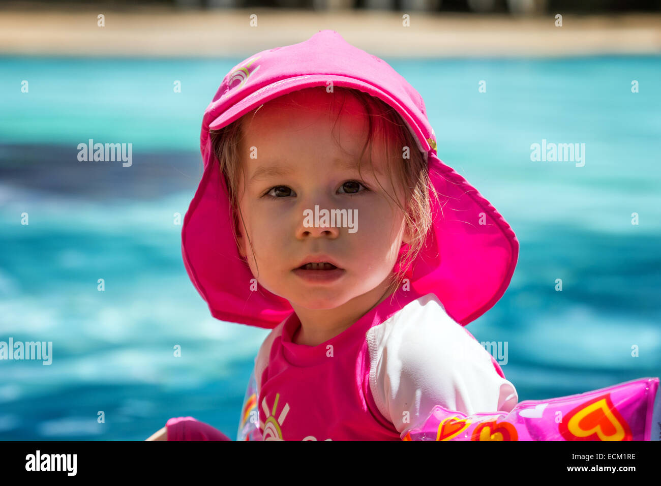 Small toddler girl by the swimming pool wearing pink UV protection swimsuit looking at camera. - Stock Image