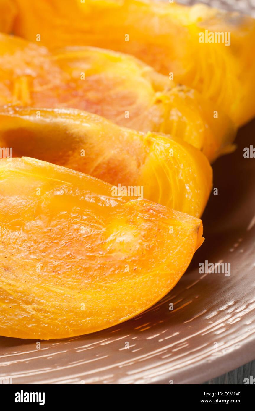 Persimmon fruit cuts on a ceramic plate, closeup - Stock Image