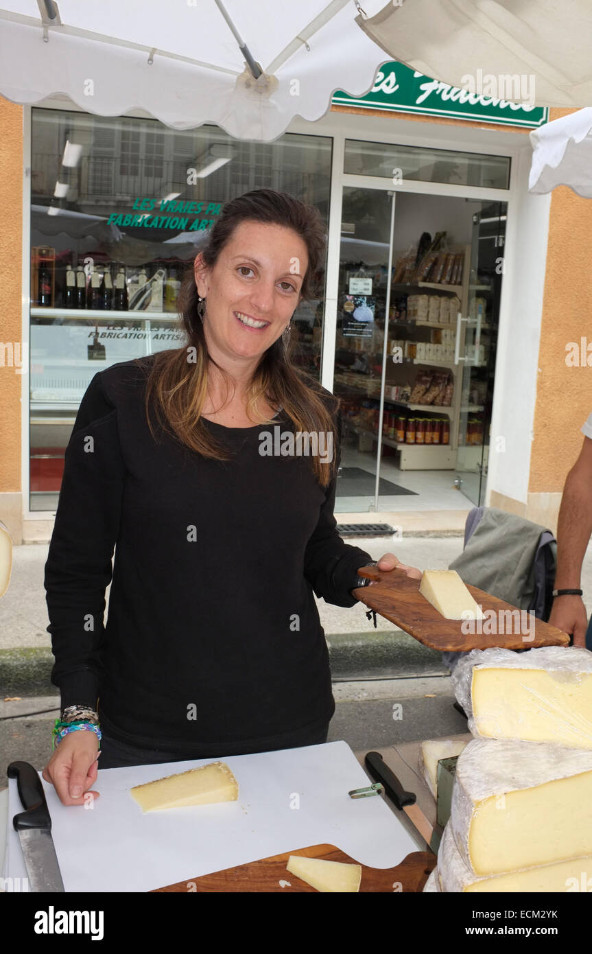 A woman selling cheese at the market in Vaison-la-Romaine, Vaucluse, Provence, France. - Stock Image