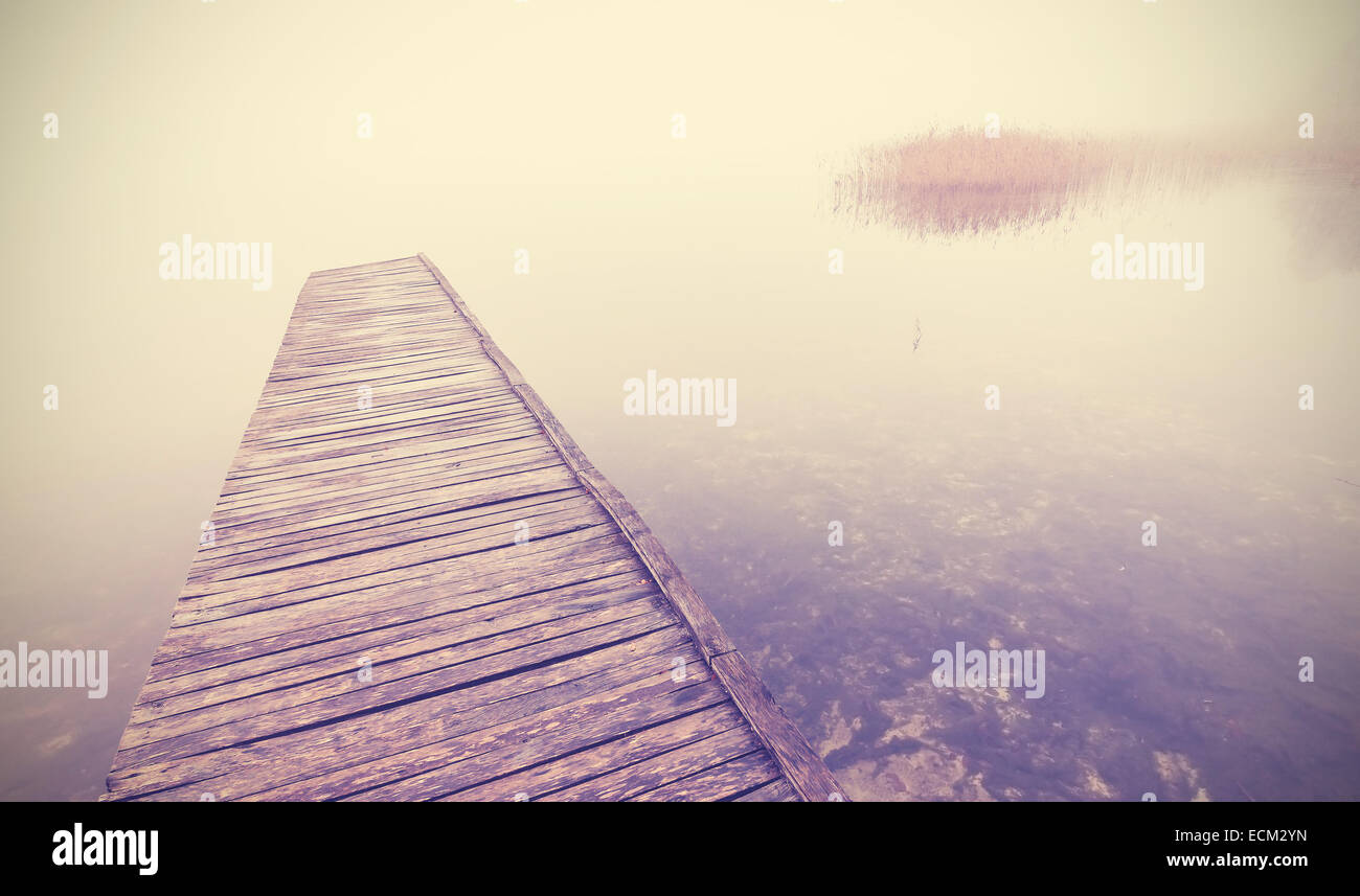 Retro filtered picture of old wooden pier into dense fog. - Stock Image