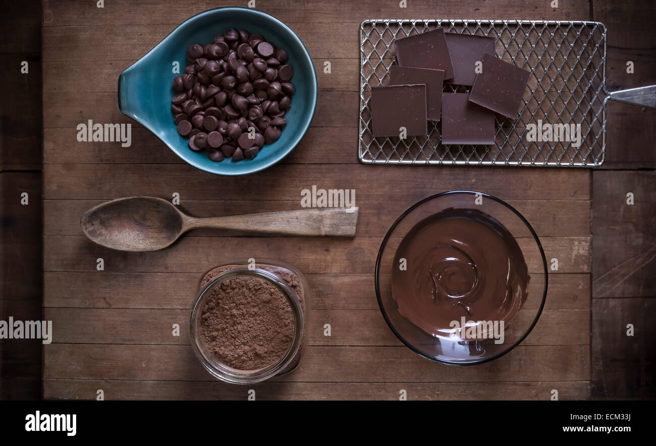 Top down view of chocolate baking supplies laid out on a rustic wood surface with antique props. Stock Photo