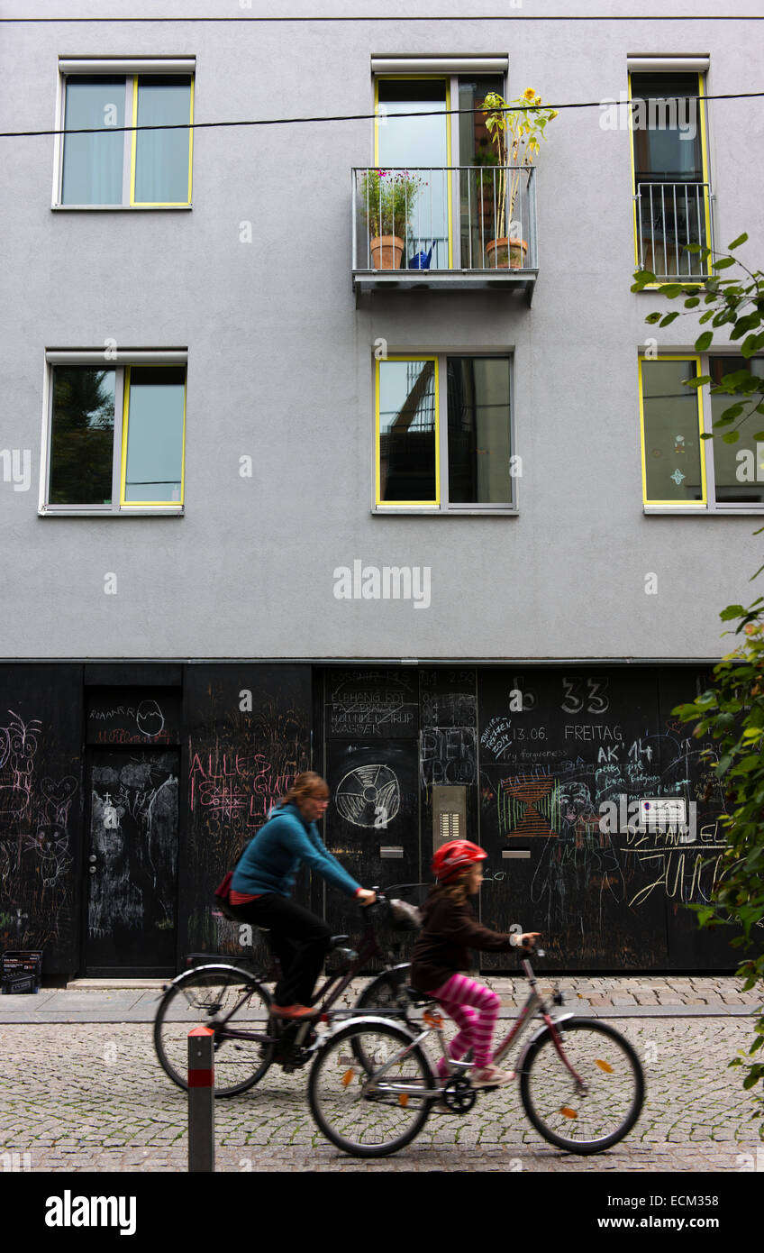 Mother and child cycling, Bohmische Strasse, Dresden's New Town.  Building walls like blackboards to combat - Stock Image