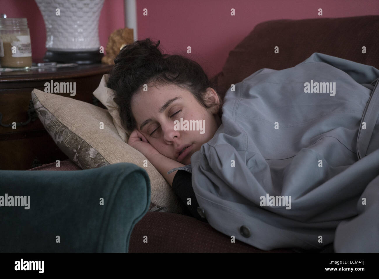Young woman takes a nap with her coat over her. Brooklyn, NY. - Stock Image