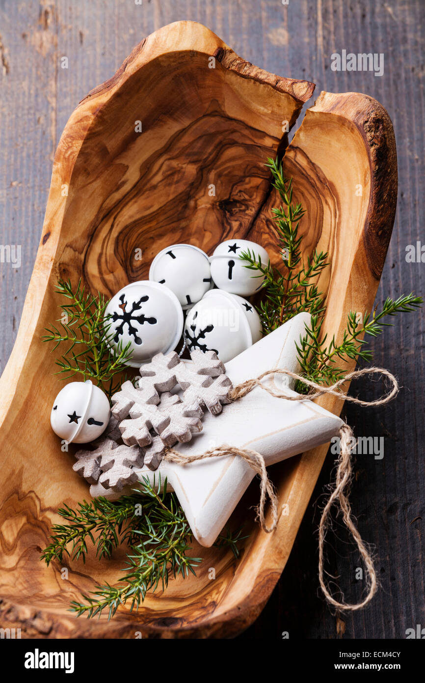 Christmas decorations Bells in olive wood bowl on green fir branches background - Stock Image