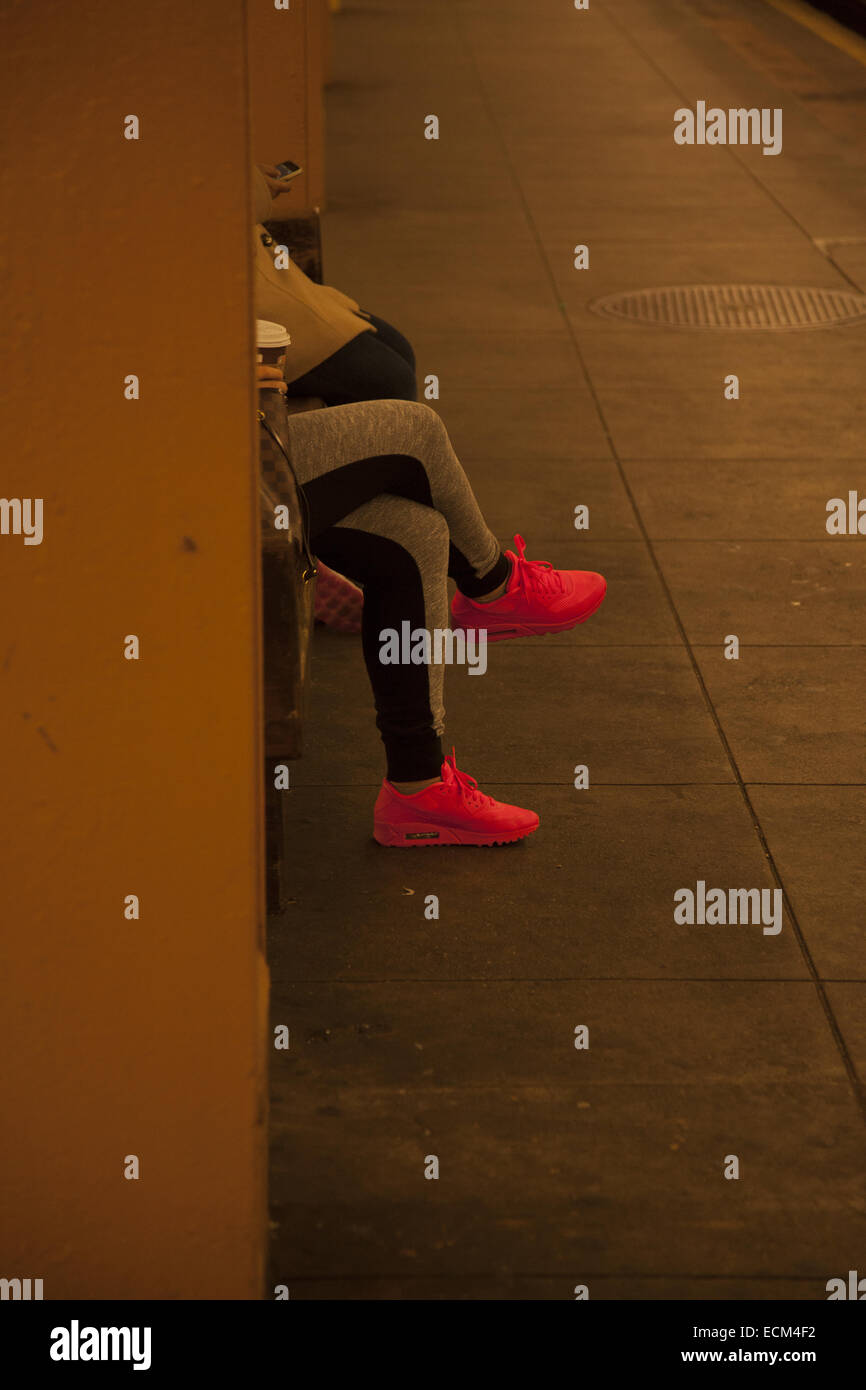 9ccdcf369b15 Woman with bright sneakers waiting for the subway at the 7th Ave. station  in Park Slope