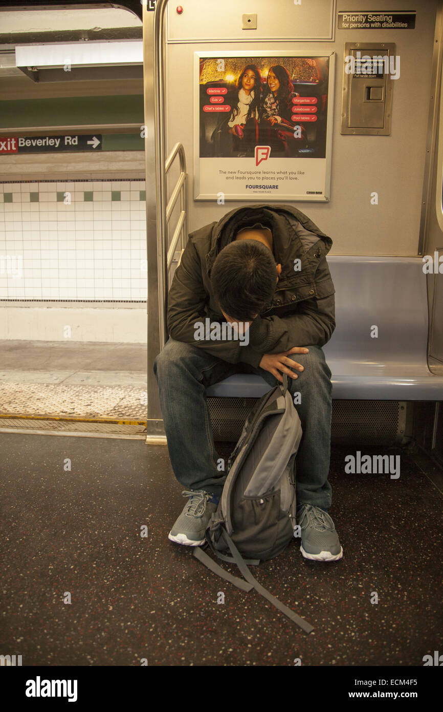 Tired high school student riding a subway train after school in Brooklyn, NY. - Stock Image
