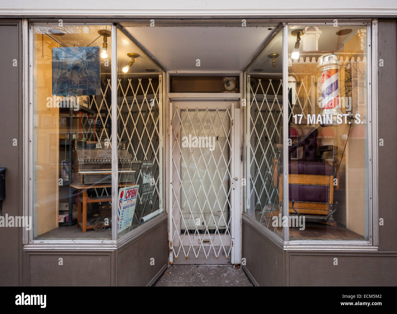 A traditional barber shop with antique furniture in the window. Downtown, Brampton, Ontario, Canada. - Stock Image