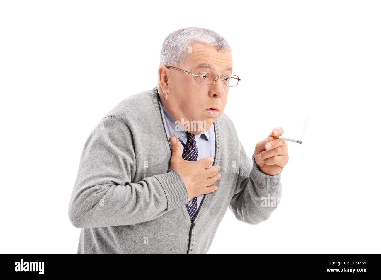 Senior man choking from the smoke of a cigarette isolated on white background - Stock Image