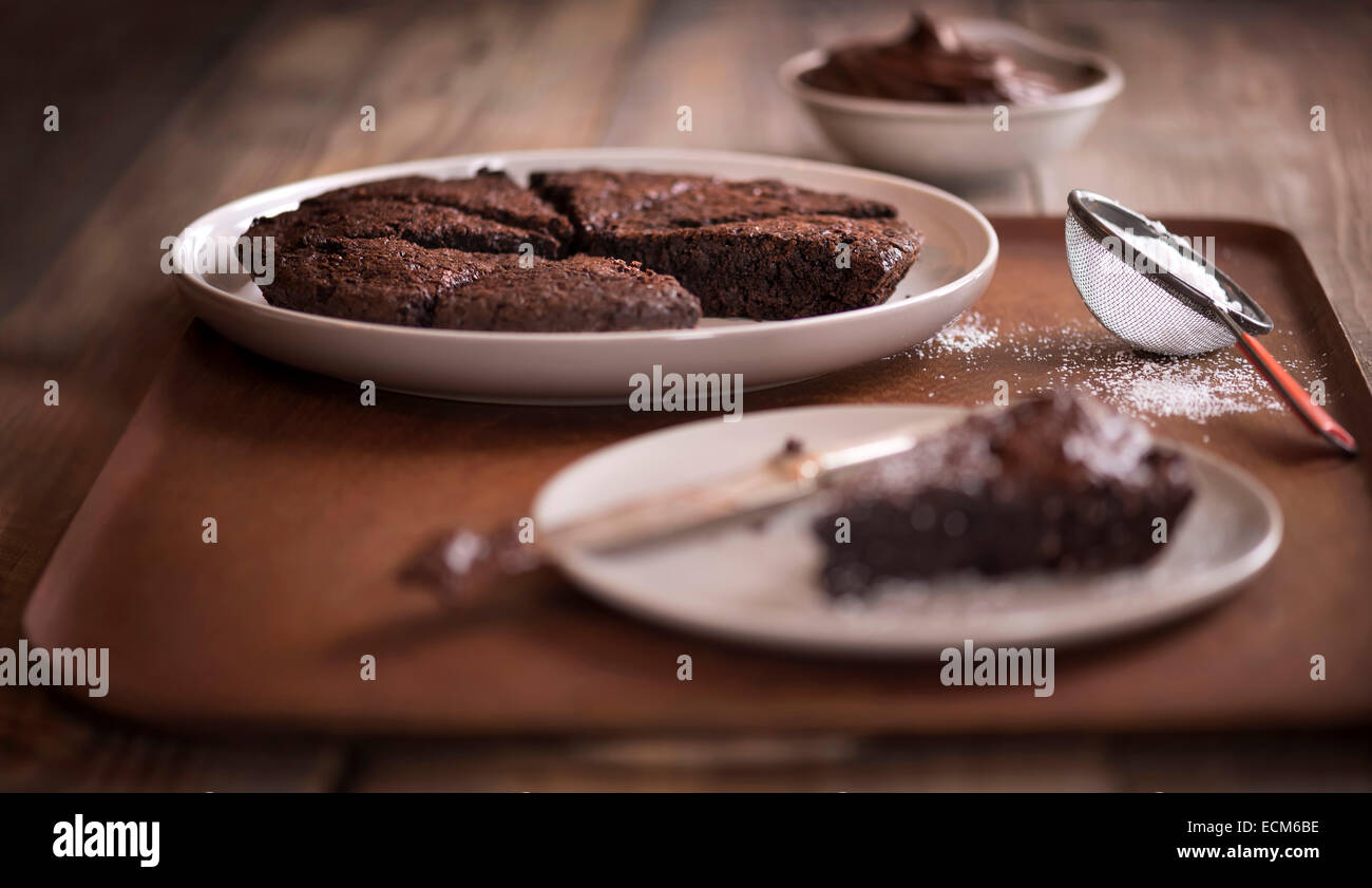 Tray of fudgy brownies with one slice on separate plate. All on an antique wood tray on a rustic wood table. - Stock Image