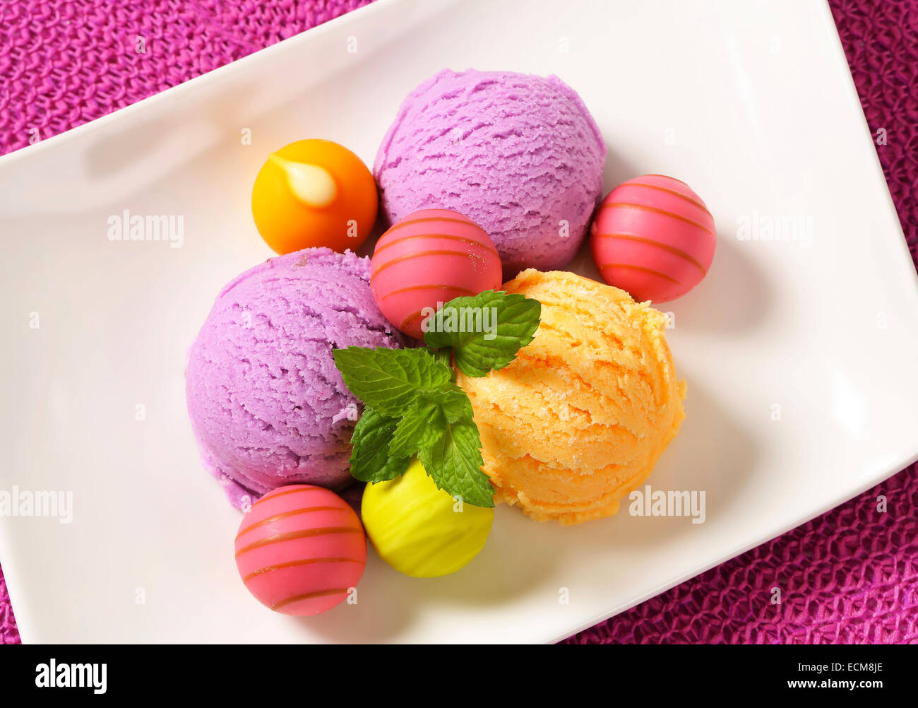 Fruit-flavored ice cream and white chocolate bonbons with fruit ganache filling - Stock Image