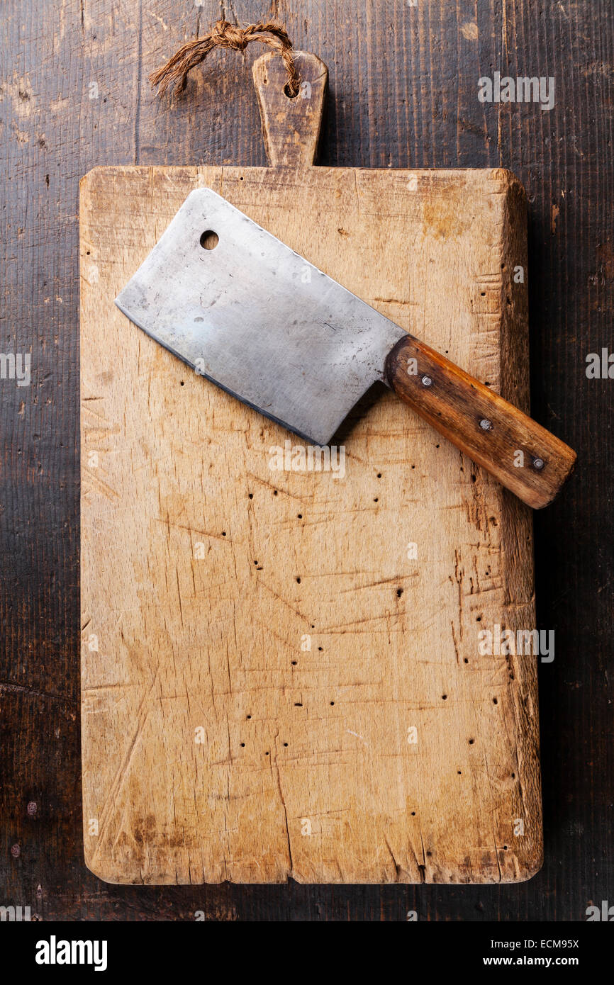 Chopping board and Meat cleaver on dark wooden background - Stock Image