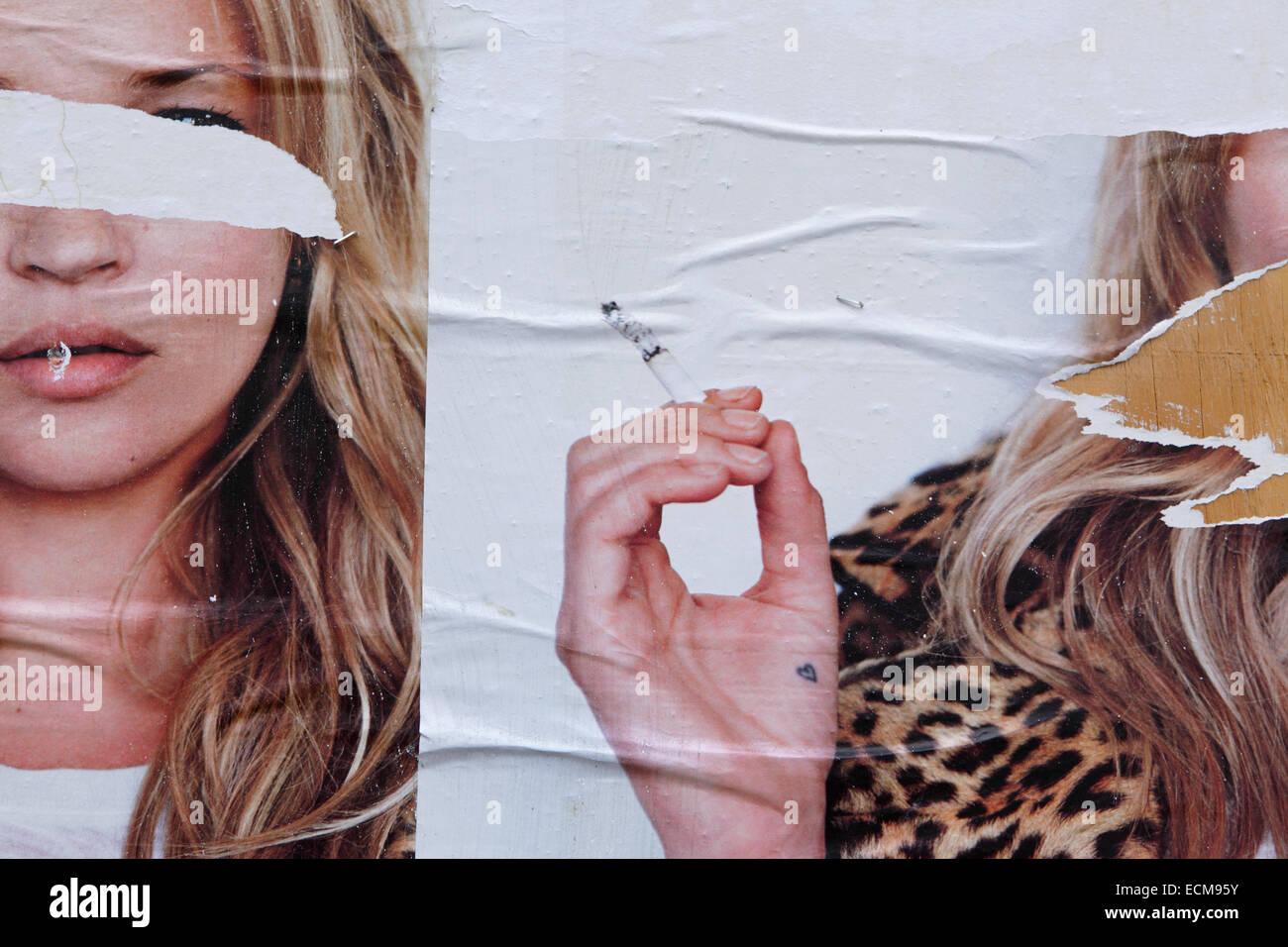 Torn billboard advertising poster of woman smoking cigarette - Stock Image