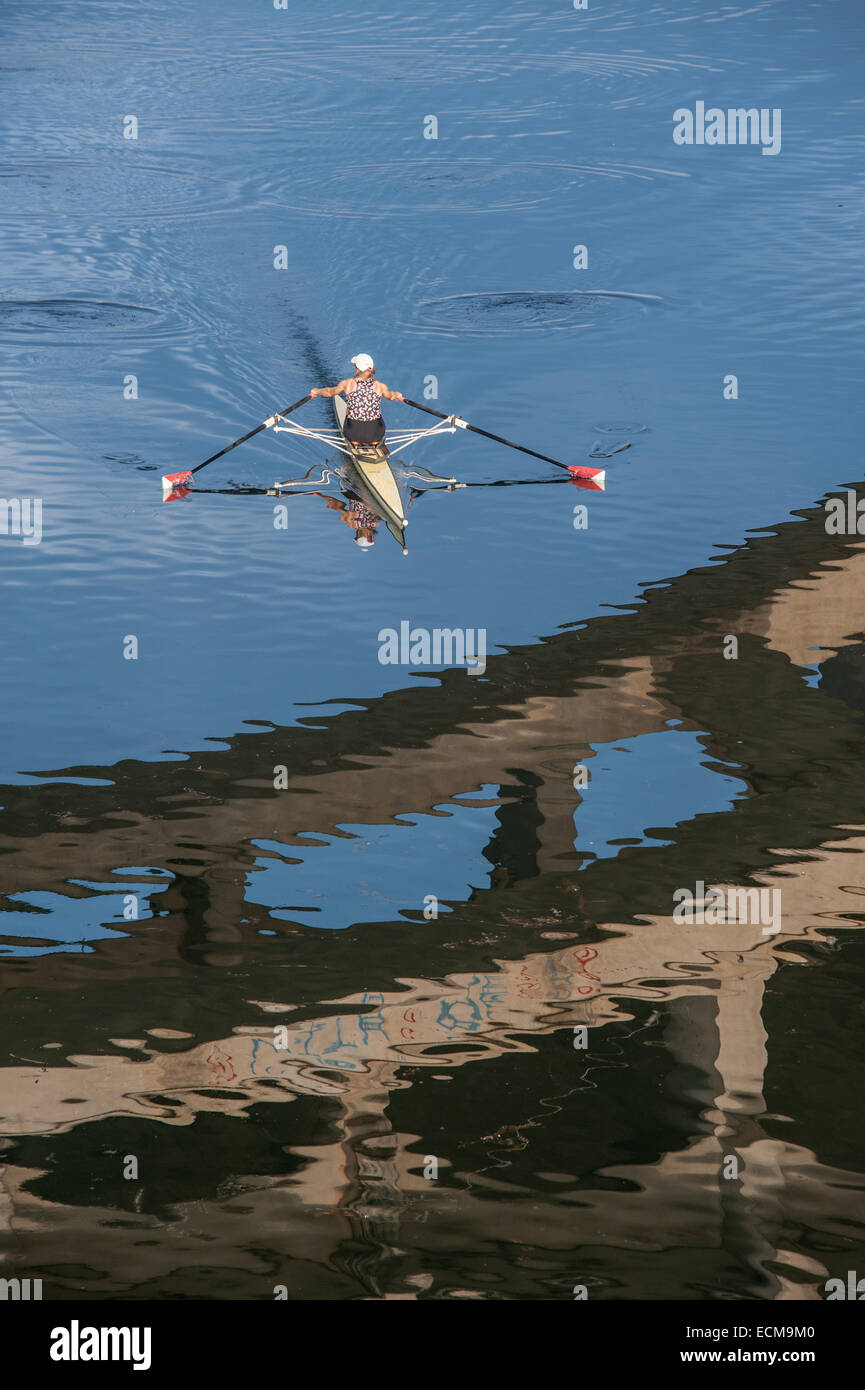 A rower on Lady Bird Lake in Austin, Texas seen with a span of the Lamar Bridge visible reflected in the water. - Stock Image