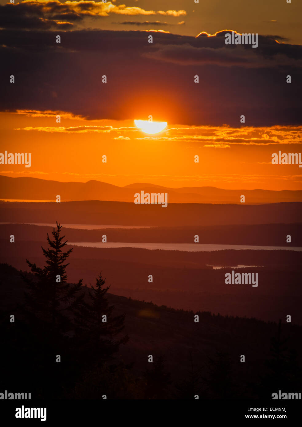 The setting sun and receding layers of hills seen from the summit of Cadillac Mountain in Acadia National Park, Stock Photo