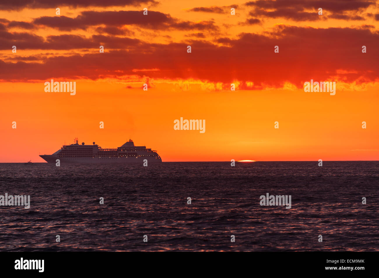 A cruise ship heads towards Bar Harbor, Maine, just as the sun begins to peek above the horizon. Stock Photo