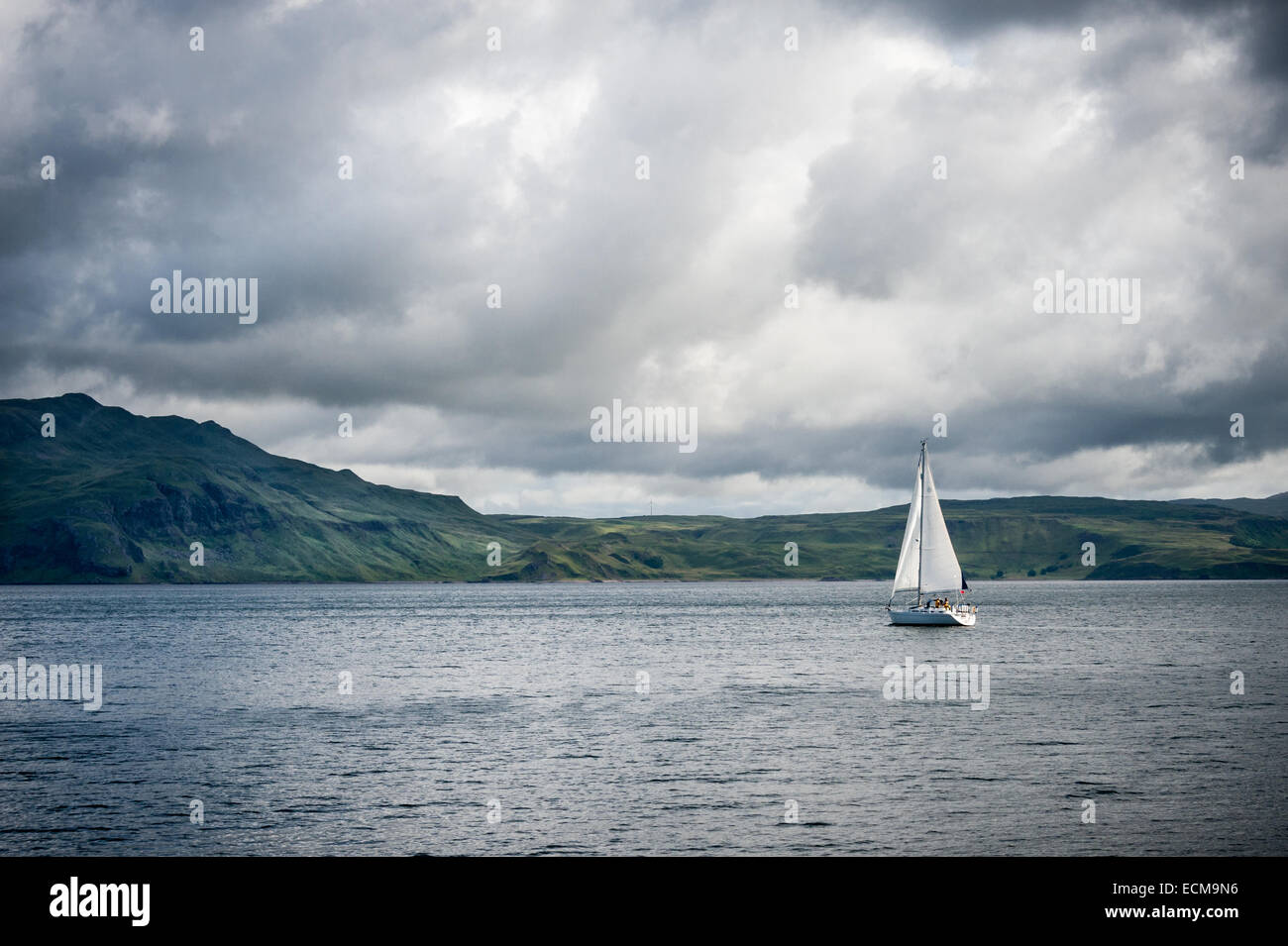 A yacht sails between the Island of Mull in the Scottish Inner Hebrides and Ardnamurchan on the mainland. Stock Photo