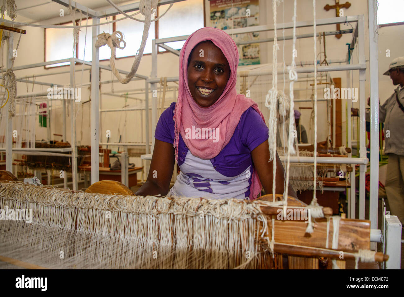 Friendly woman working on a hand weaving loom in a social project, Eritrea - Stock Image